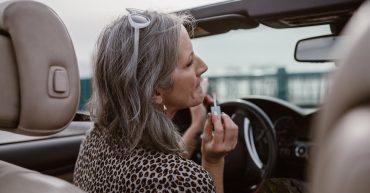Žena v strednom veku sa maľuje v aute